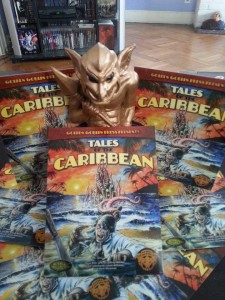 """Image is 5 books laid out in presentation around a statuette of a golden goblin. The books itself features the text """"Tales of the Caribbean"""" it features a man approaching the bottom edge of the cover with the ocean extending up behind him. In the ocean is some sort of tentacled thing with tentacles reaching towards him."""